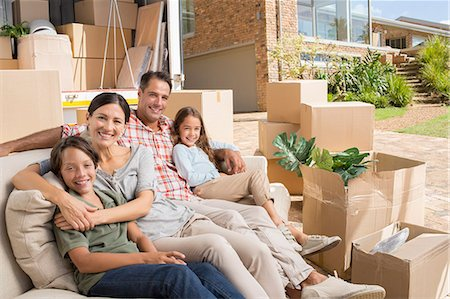 Portrait of smiling family sitting on sofa near moving van in driveway Stock Photo - Premium Royalty-Free, Code: 6113-07147177