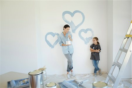 Mother and daughter painting blue hearts on wall Stock Photo - Premium Royalty-Free, Code: 6113-07147195