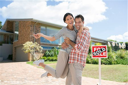 Portrait of enthusiastic couple hugging outside house with For Sale sign Stock Photo - Premium Royalty-Free, Code: 6113-07147135