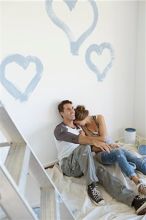 Couple painting blue hearts on wall Stock Photo - Premium Royalty-Free, Code: 6113-07147136