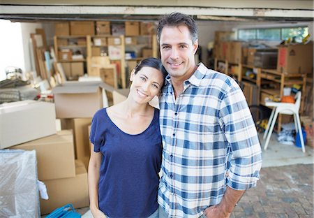 Portrait of smiling couple outside garage among cardboard boxes Stock Photo - Premium Royalty-Free, Code: 6113-07147241