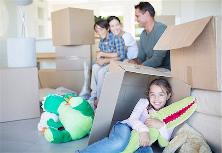 Family among cardboard boxes in livingroom Stock Photo - Premium Royalty-Free, Code: 6113-07147242