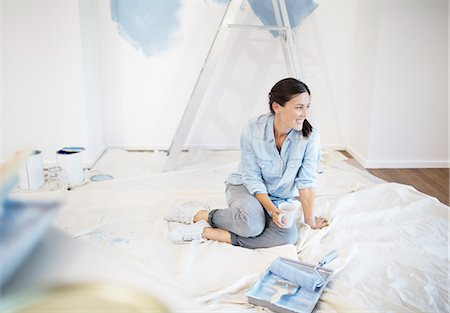 Woman drinking coffee surrounded by painting supplies Stock Photo - Premium Royalty-Free, Code: 6113-07147249