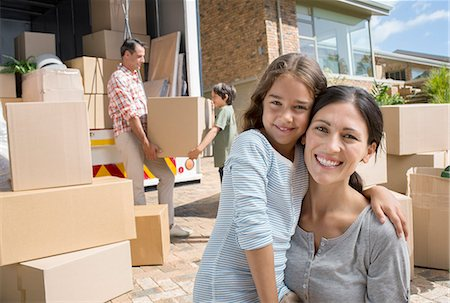 Mother and daughter smiling by moving van in driveway Stock Photo - Premium Royalty-Free, Code: 6113-07147250