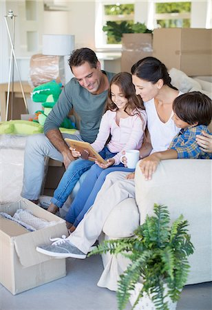 four - Family looking at picture frame on sofa among cardboard boxes Stock Photo - Premium Royalty-Free, Code: 6113-07147256