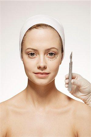 Plastic surgeon marking woman's face Stock Photo - Premium Royalty-Free, Code: 6113-07147266