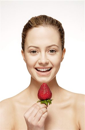 Smiling woman eating strawberry Stock Photo - Premium Royalty-Free, Code: 6113-07147268
