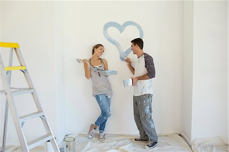 Couple painting blue heart on wall Stock Photo - Premium Royalty-Free, Code: 6113-07147202