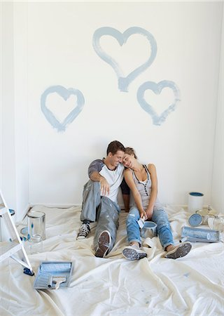 Couple painting blue hearts on wall Stock Photo - Premium Royalty-Free, Code: 6113-07147208