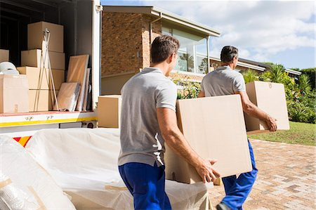 Movers carrying boxes in new house Stock Photo - Premium Royalty-Free, Code: 6113-07147210