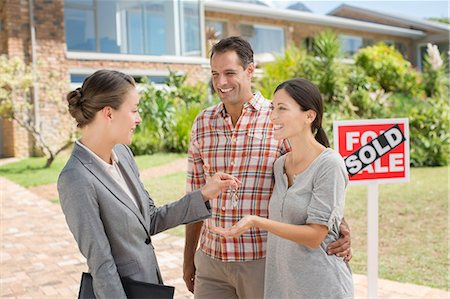 sold sign - Realtor giving couple keys to new house Stock Photo - Premium Royalty-Free, Code: 6113-07147217