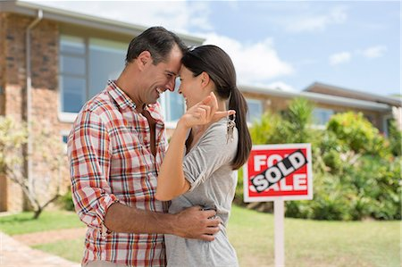 sold sign - Couple hugging outside new house Stock Photo - Premium Royalty-Free, Code: 6113-07147214