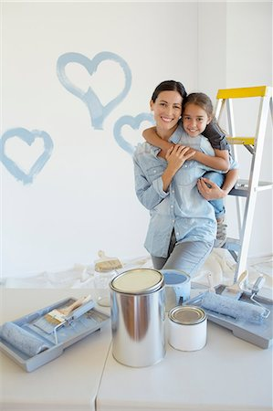 Mother and daughter hugging among paint supplies Stock Photo - Premium Royalty-Free, Code: 6113-07147218