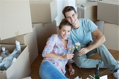 Portrait of couple enjoying champagne among cardboard boxes Stock Photo - Premium Royalty-Free, Code: 6113-07147220