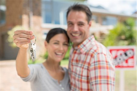 sold sign - Portrait of smiling couple holding house keys Stock Photo - Premium Royalty-Free, Code: 6113-07147221