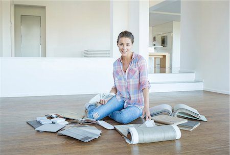 Woman viewing carpet and paint swatches in empty living room Stock Photo - Premium Royalty-Free, Code: 6113-07147222