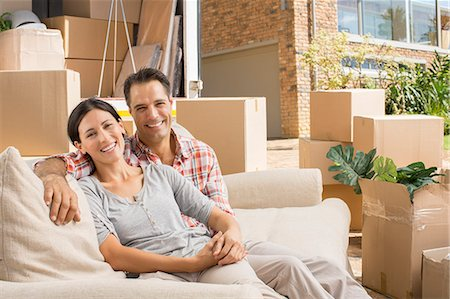 Portrait of smiling couple on sofa near moving van in driveway Stock Photo - Premium Royalty-Free, Code: 6113-07147224