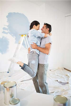 Couple hugging among paint supplies Stock Photo - Premium Royalty-Free, Code: 6113-07147225