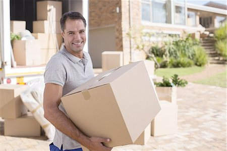 Portrait of man carrying cardboard box from moving van Stock Photo - Premium Royalty-Free, Code: 6113-07147230