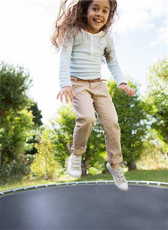 Girl jumping on trampoline outdoors Stock Photo - Premium Royalty-Free, Code: 6113-07147232