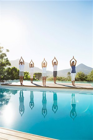 People practicing yoga at poolside Stock Photo - Premium Royalty-Free, Code: 6113-07147376
