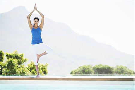 Woman practicing yoga at poolside Stock Photo - Premium Royalty-Free, Code: 6113-07147379