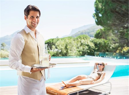 people and vacation - Waiter smiling at poolside Stock Photo - Premium Royalty-Free, Code: 6113-07147468