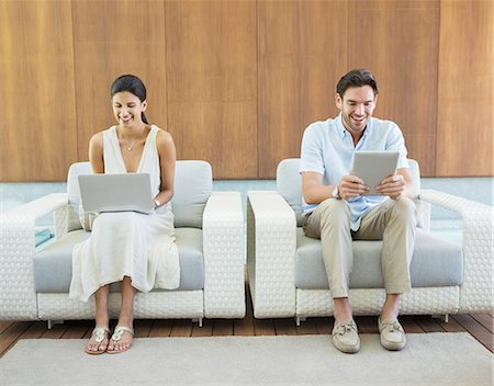 Couple using laptop and digital tablet in armchairs Stock Photo - Premium Royalty-Free, Code: 6113-07147476
