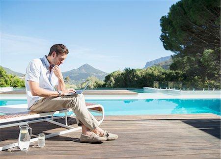 swimming pool water - Man using laptop at poolside Stock Photo - Premium Royalty-Free, Code: 6113-07147479