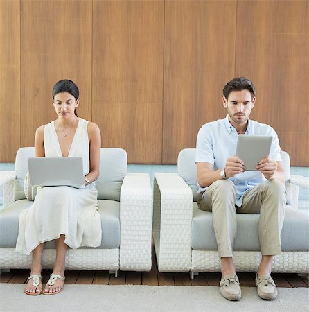 Couple using digital tablet and laptop in armchairs Stock Photo - Premium Royalty-Free, Code: 6113-07147487