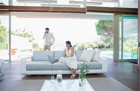 rich lifestyle - Couple using cell phone and laptop in living room Stock Photo - Premium Royalty-Free, Code: 6113-07147488