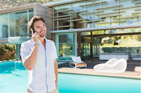 rich lifestyle - Man talking on cell phone at poolside Stock Photo - Premium Royalty-Free, Code: 6113-07147490