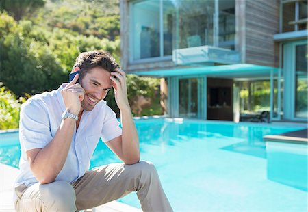 rich lifestyle - Man talking on cell phone at poolside Stock Photo - Premium Royalty-Free, Code: 6113-07147497