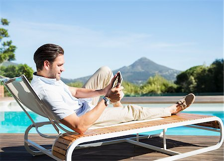 Man using digital tablet on lounge chair at poolside Stock Photo - Premium Royalty-Free, Code: 6113-07147494