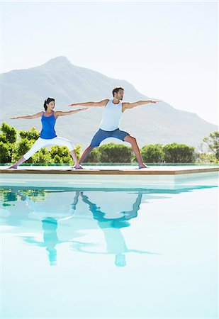 Couple practicing yoga at poolside Stock Photo - Premium Royalty-Free, Code: 6113-07147404