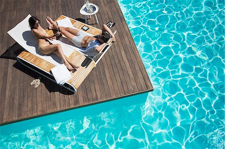 pool - Couple laying on lounge chair at poolside Stock Photo - Premium Royalty-Free, Code: 6113-07147406
