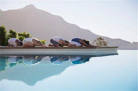 People practicing yoga at poolside Stock Photo - Premium Royalty-Free, Code: 6113-07147412