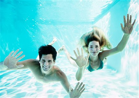 Portrait of smiling couple underwater in pool Stock Photo - Premium Royalty-Free, Code: 6113-07147423