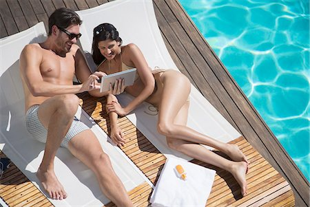 Couple using digital tablet poolside Stock Photo - Premium Royalty-Free, Code: 6113-07147422