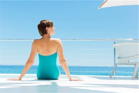 rich lifestyle - Woman relaxing poolside with ocean in background Stock Photo - Premium Royalty-Free, Code: 6113-07147511