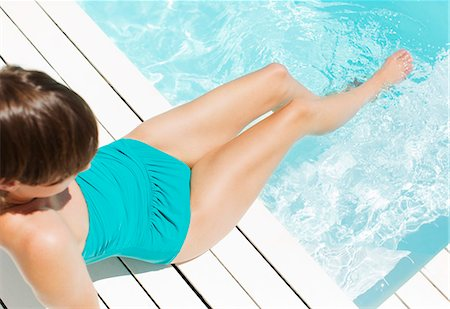 Woman in bathing suit relaxing poolside Stock Photo - Premium Royalty-Free, Code: 6113-07147527