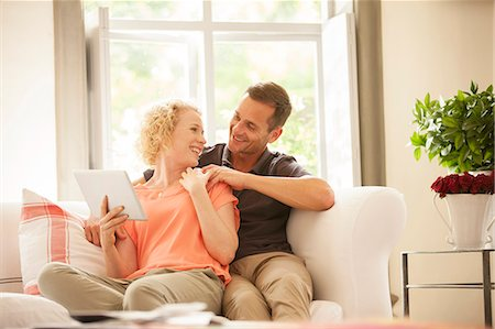 Couple using digital tablet on sofa Stock Photo - Premium Royalty-Free, Code: 6113-07147656