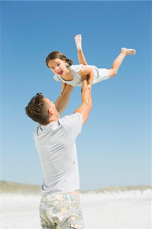 Father lifting daughter overhead on beach Stock Photo - Premium Royalty-Free, Code: 6113-07147697