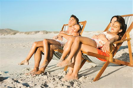 Family sleeping in lounge chairs on beach Stock Photo - Premium Royalty-Free, Code: 6113-07147743