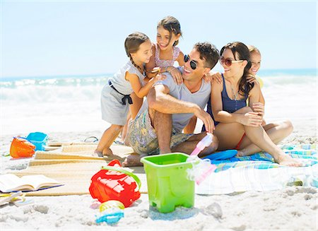 families playing on the beach - Family hugging on blanket at beach Stock Photo - Premium Royalty-Free, Code: 6113-07147756
