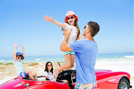 Father lifting daughter from convertible at beach Stock Photo - Premium Royalty-Free, Code: 6113-07147762