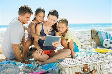 families playing on the beach - Family using digital tablet on beach Stock Photo - Premium Royalty-Free, Code: 6113-07147777