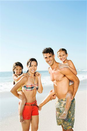 Parents carrying daughters piggyback on beach Stock Photo - Premium Royalty-Free, Code: 6113-07147776