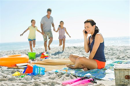 families playing on the beach - Woman talking on cell phone at beach Stock Photo - Premium Royalty-Free, Code: 6113-07147779