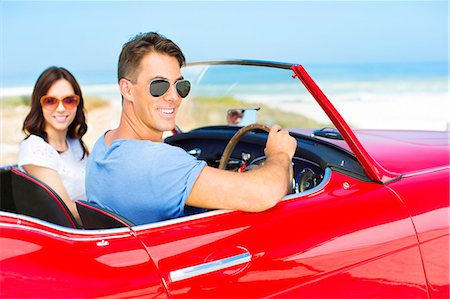Couple driving convertible on beach Stock Photo - Premium Royalty-Free, Code: 6113-07147784